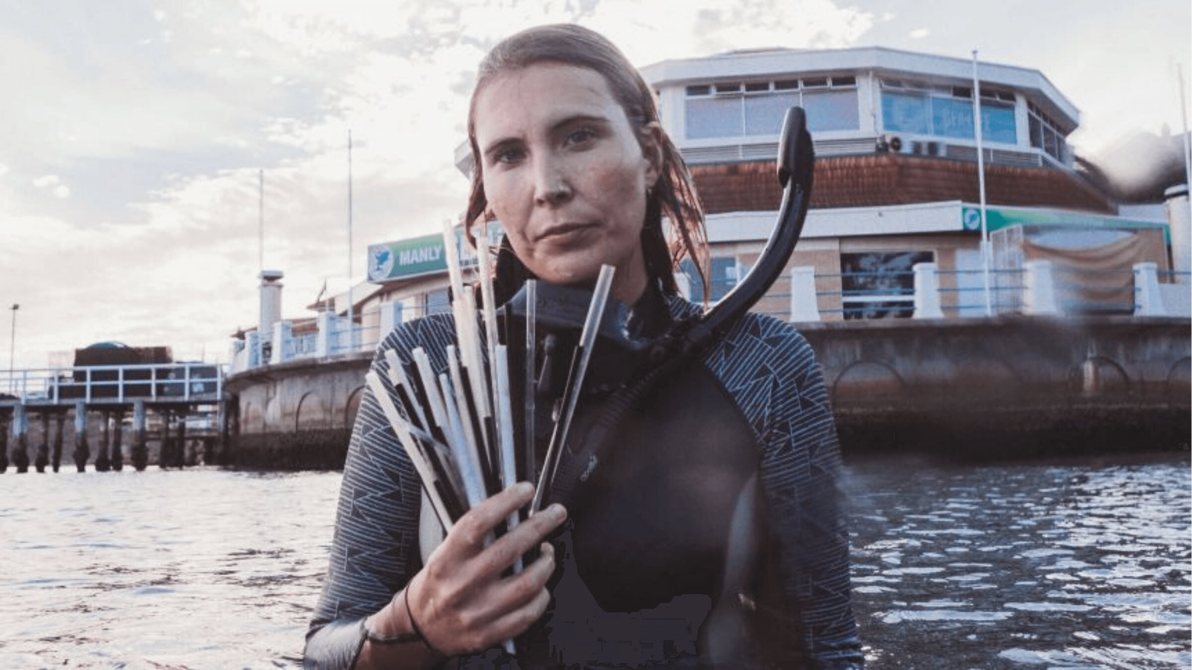 A woman holding a bunch of straws in front of the sea