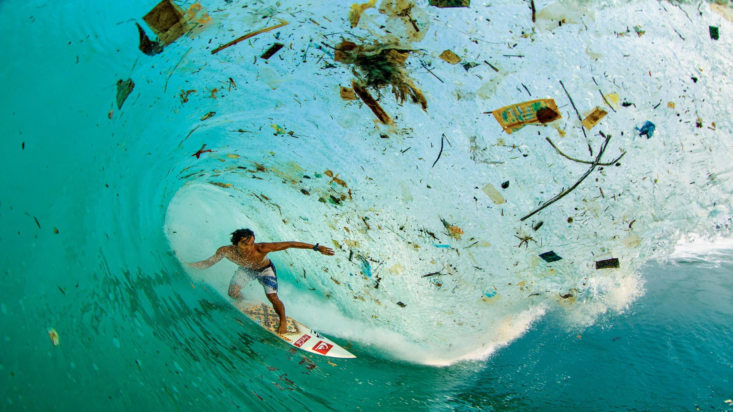 A man surfing in waves with plastic in them