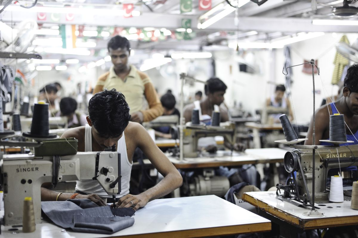 A man working in Dharavi, India to make clothes for the fast-fashion industry at minimum wage