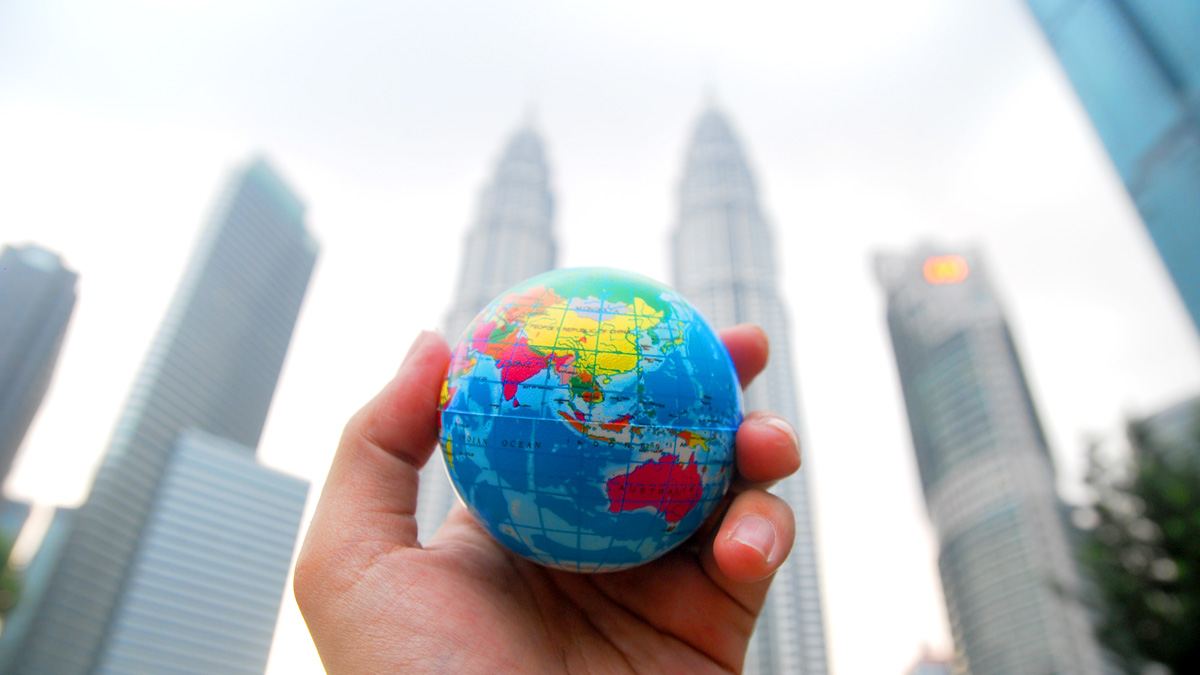 A hand with a globe in their palm in front of high-rise buildings