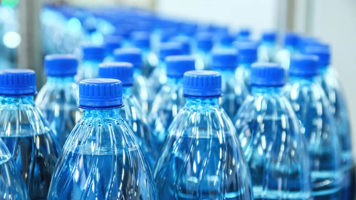 A row of single-use bottled plastic water bottles