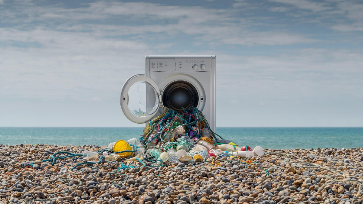 A washing machine with plastic coming our of it on a sea coast