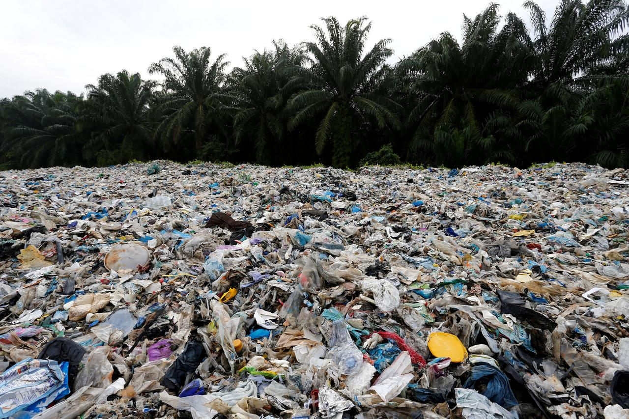 A beach coast covered with plastic waste  with palm tress in the background