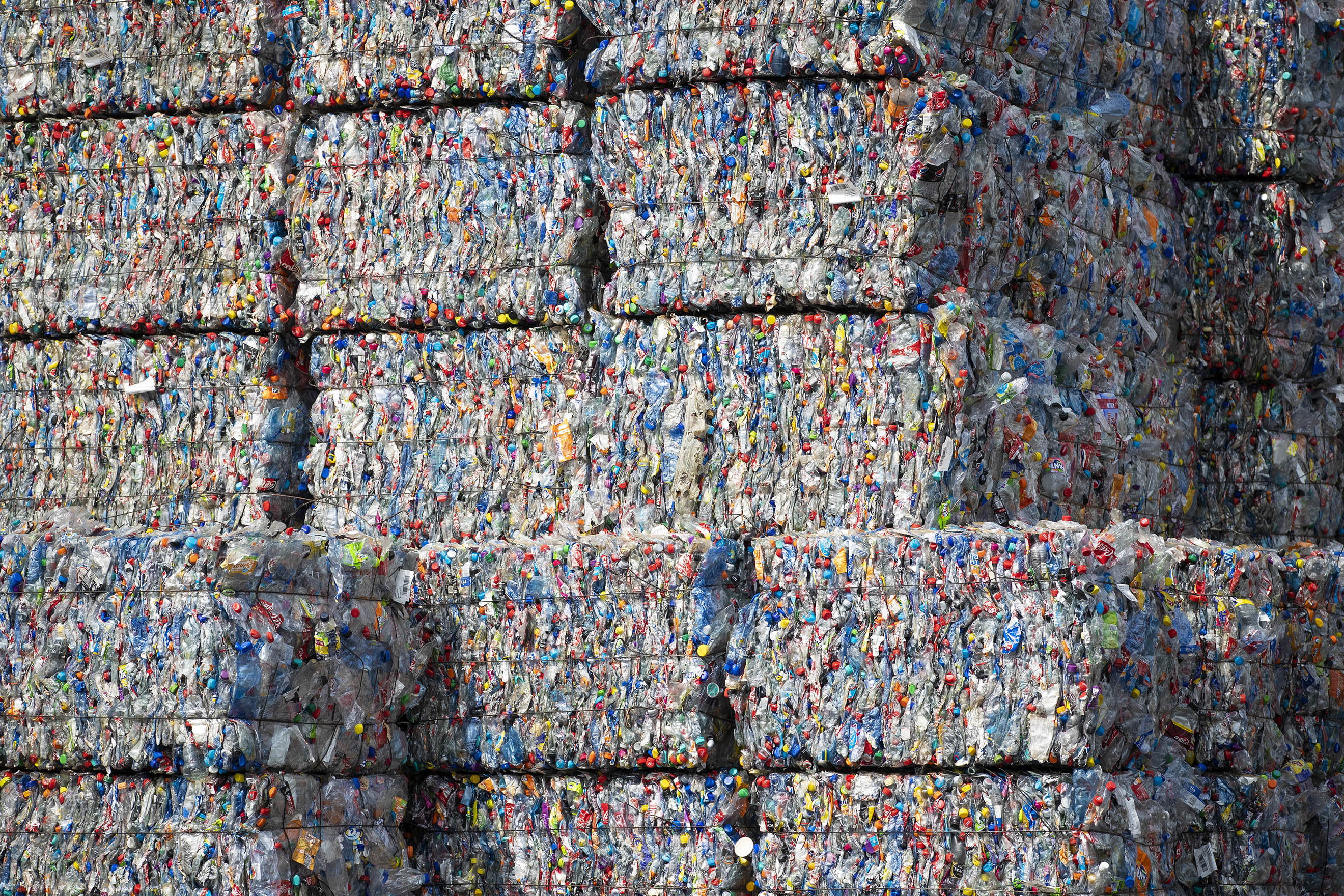 Bound bales of crushed plastic as part of developed countries exported waste waiting to be recycled