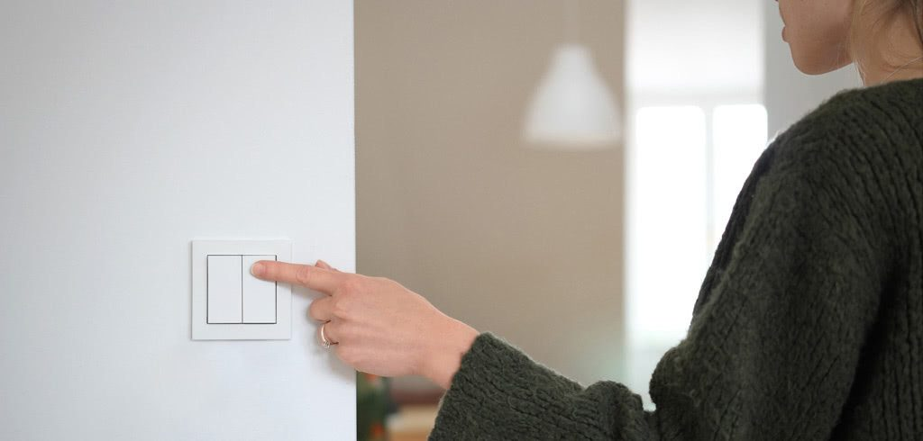 A woman switching off the lights before leaving the room as a part of a sustainable lifestyle
