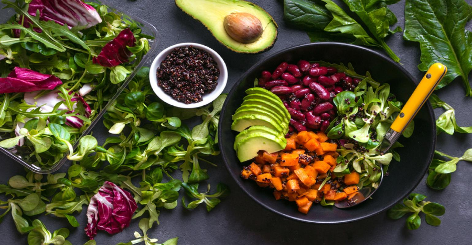A vegan food bowl with vegetables and fruits around it