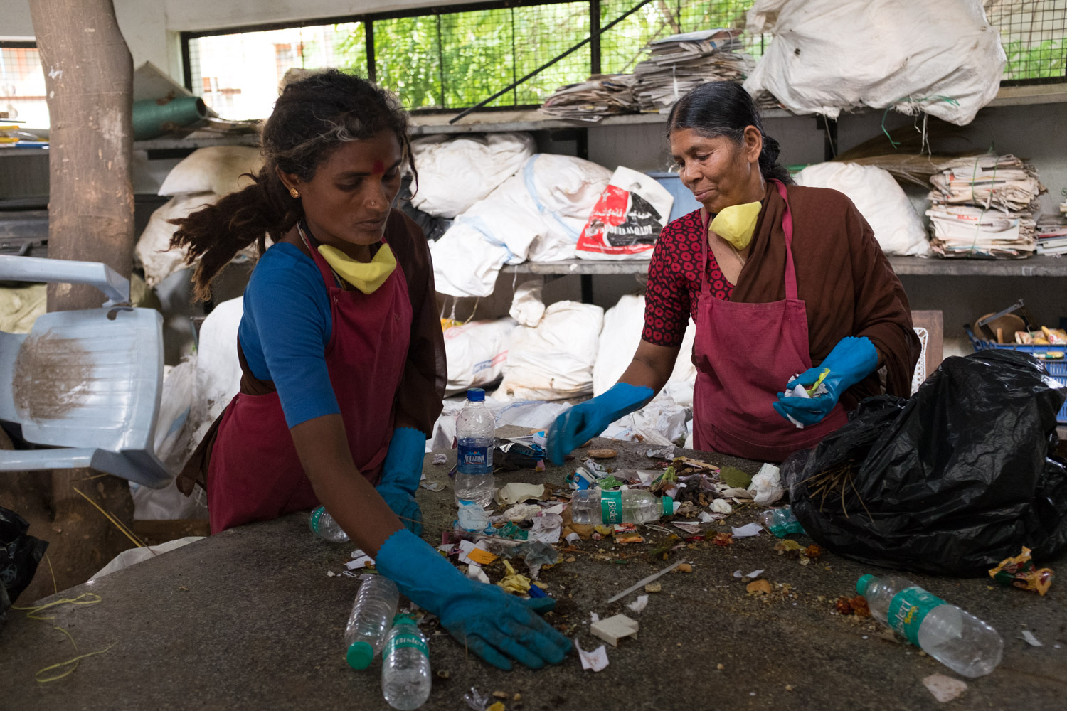 2 women sorting out waste at a recycling enterprise in India