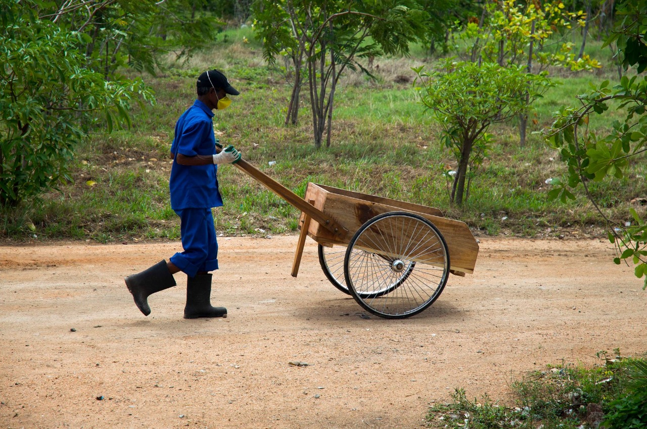 A waste worker from Waste Ventures India moving a wheel barrow