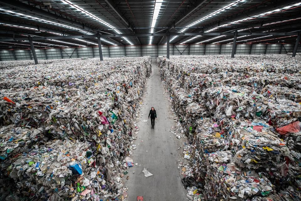 A person walking between piles of plastic stacked up
