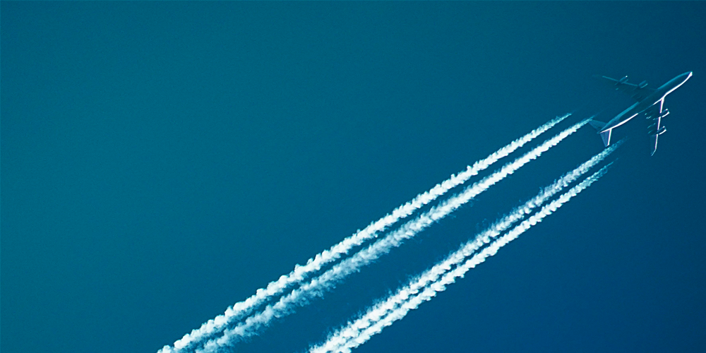 An airplane in the sky with a jetstream