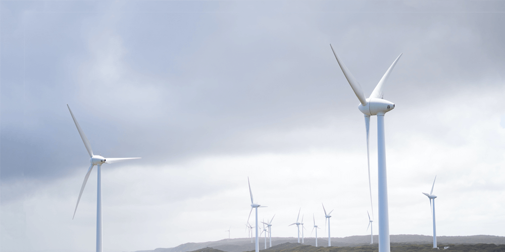 Rotating wind turbines with the backdrop of a grey sky