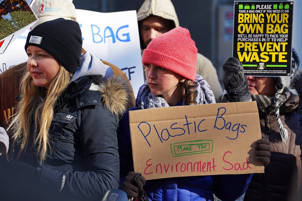 People at a rally holding up posters to implore the government to ban plastic bags