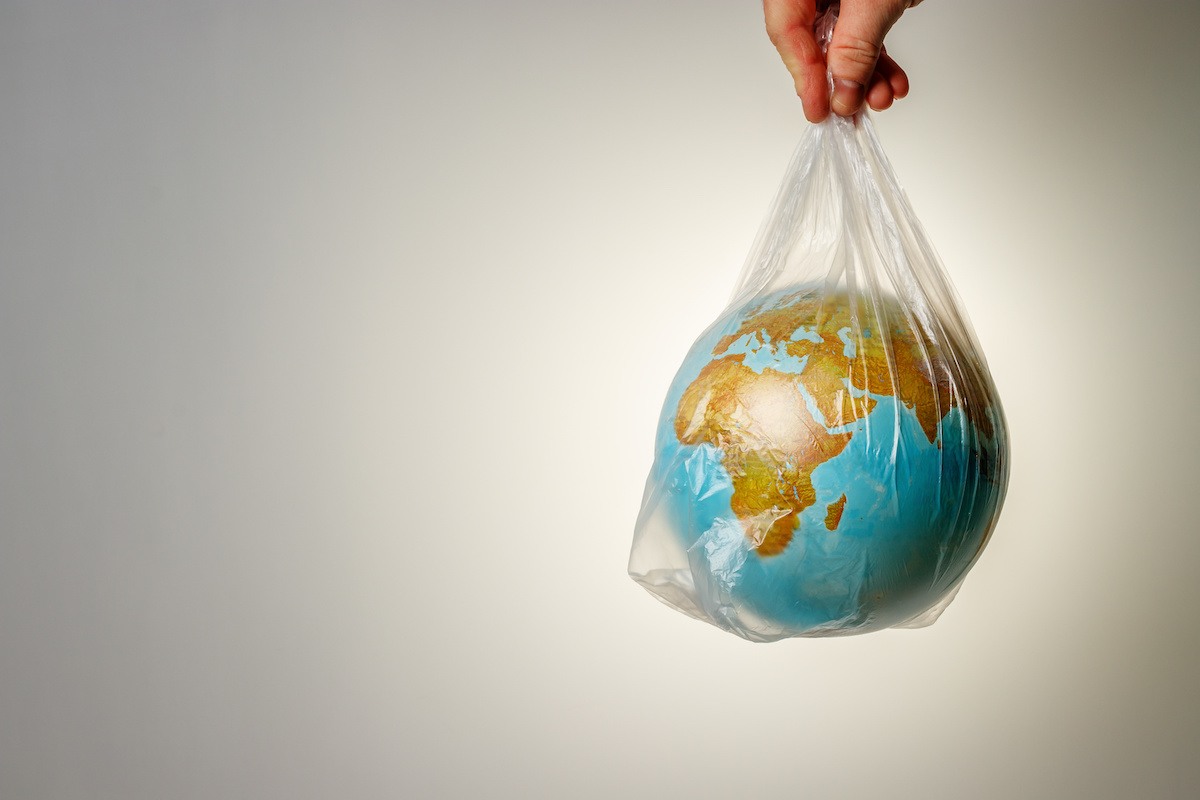 Image of a hand holding the earth in a plastic bag