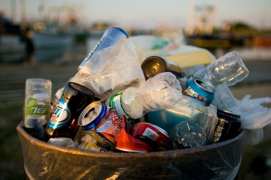 A trash can full of beverage cans and bottles which are one of the major contributors to plastic pollution