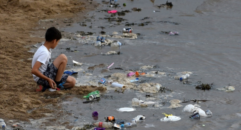 A beach with plastic waste littered all over it in UK