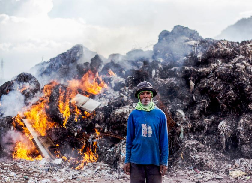 An Indonesian man standing in front of a pile of burning plastic causing air pollution