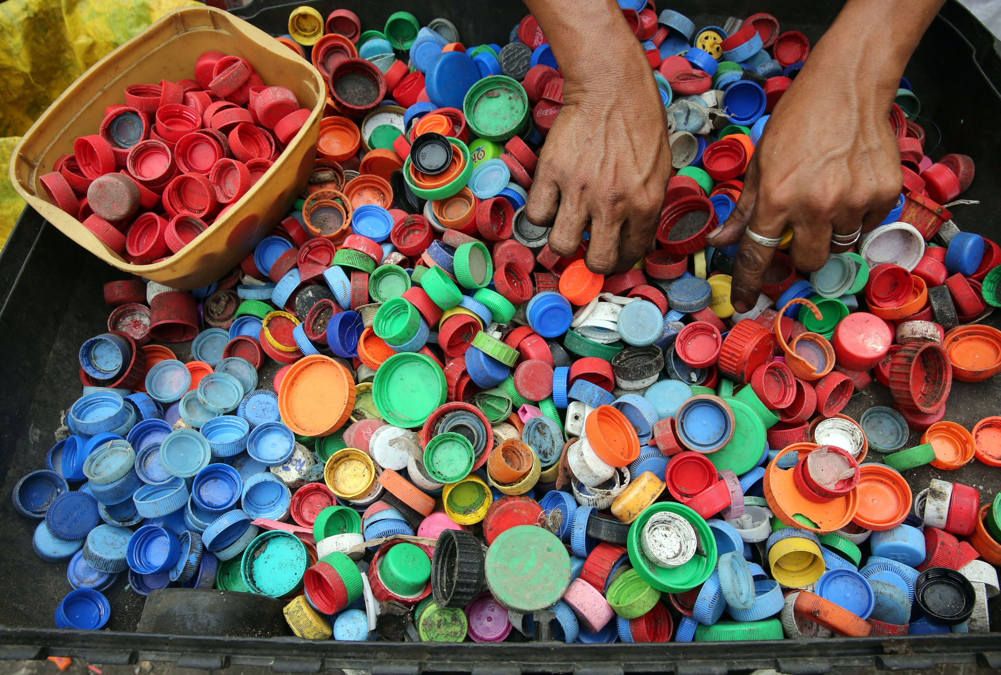 A man sorting through bottle and container caps which are one of the major contributors to plastic pollution